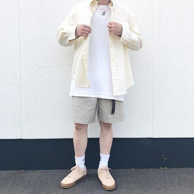 白シャツに薄黄色の長袖シャツを合わせた淡い色合いの大人カジュアルコーデ